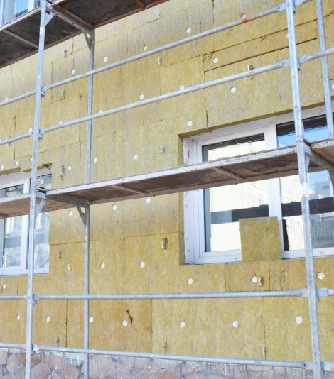 Install Rock Mineral Wool Insulation. Energy efficiency house wall  renovation for energy saving. Exterior house wall heat insulation with mineral wool, building under construction.